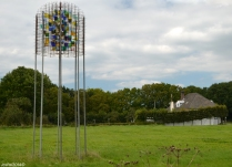 Maas Beacon by Herman Coppus. With the sky as a background one sees a metal tower construction standing in a meadow. Glass has been incorporated in the top, in the colours of the area around the river Maas. One can recognize the hues of water, sky and nature. A colourful beacon in a riverscape.